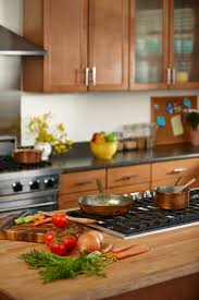 butcher block counters surround an island stove top kitchen