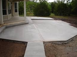 grey concrete floor patio with grey stone fire pit and grey chair