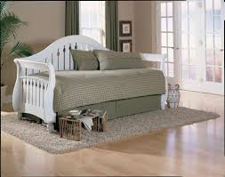white wood twin sleigh style daybed with trundle and grey skirt