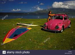 pink volkswagen beetle a woman in a stands at a pink volkswagen beetle with a