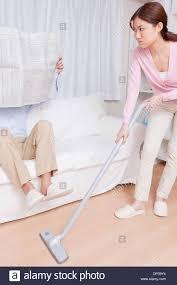 Vaccuming Young Woman Vacuuming Man Reading Newspaper Stock Photo Royalty