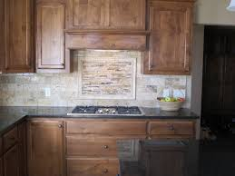 kitchen back splash with decorative piece over cooktop subway