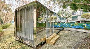 mirrored shipping container building reflects its natural
