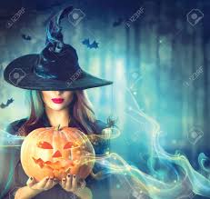 halloween witch with a magic pumpkin in a dark forest stock photo