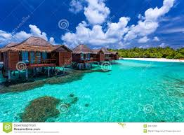 over water bungalows with steps into green coral lagoon stock