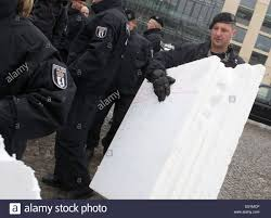 police offficers remove polystyrene sheets while asylum seekers