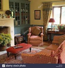 yellow livingroom patterned red sofa and armchair in livingroom with pale yellow