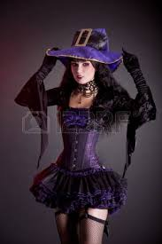 smiling witch in purple and black gothic halloween costume studio