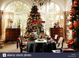 decorated christmas tree in a conservatory with a decorative table