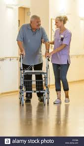 Home Nurse by Elderly Care In A Nursing Home Nurse Helps An Elderly Man Walking