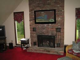 black fireplace on the brown brick wall completed with large tv