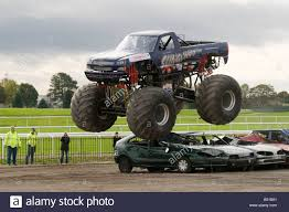 racing monster truck monster truck jumping crushed cars in a race stock photo royalty