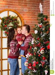 dad and mom kissing baby in a christmas party at the tree stock