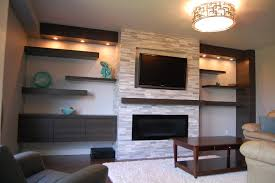 white stone fireplace with black led tv and black wooden shelves