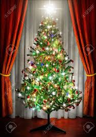 sparkling christmas tree in a room next to window curtains stock