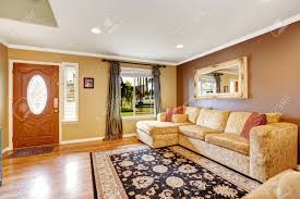 living room with brown and ivory color walls creamy tone sofa