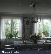 swedish country white voile curtains on windows in swedish country dining room