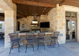 exterior outdoor kitchen with bar area and corner wall mounted