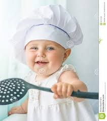 cuisine de bébé bébé dans le chef de capot avec l outil de cuisine photo stock