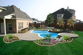 white pool with small garden and green grass yard plus brown