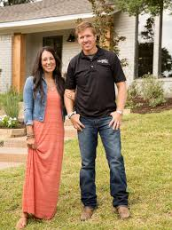 fixer upper hosts chip and joanna gaines standing in front of the