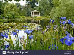 large english country garden with gazebo viewed across a lake with