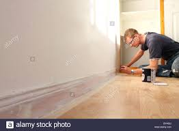 Skirting Board Laminate Flooring Man Painting Skirting Board In A Uk Home Stock Photo Royalty Free