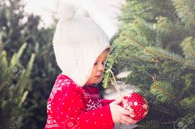 cute baby in red scandinavian dress at the christmas tree
