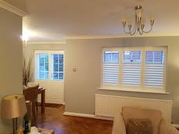 plantation shutters for living room window and french doors of