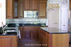glass and stainless steel backsplash white particle board cabinets