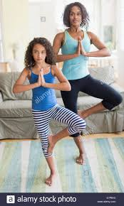 mother and daughter 8 9 doing in yoga poses in living room stock