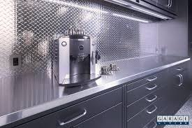 the underground garage remodel garage living gl custom steel cabinetry with a stainless steel countertop and diamond plate backsplash an espresso machine in the garage with countertops this clean