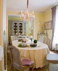 french country style dining room with yellow walls and chandelier