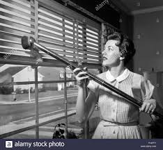 1950s woman vacuuming venetian blinds on window looking out onto