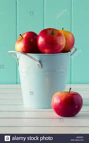 bucket full of apples on a white wooden table with a robin egg