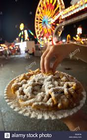 person eating funnel cake enjoying the amusement park at the
