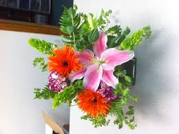cube arrangement with bells of ireland pink lilies orange spider