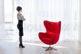 Bright Armchair Portrait Of A Young Woman Looking Into The Camera On The