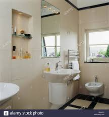 mirror above wall mounted basin in modern tiled bathroom with