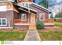 two level house exterior with wooden panel trim and porch stock