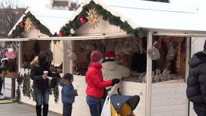 people walk around the christmas white wooden market stall in