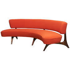 curved floating sofa on sculptured walnut legs by vladimir kagan