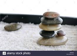 smooth rocks stacked in a miniature zen rock garden sandbox stock