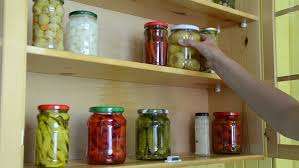 hand take from shelves in kitchen cupboard different size jars