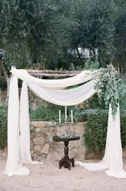 wedding arch leaves green leaves accent a wooden arbor draped with fabric to