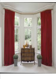 noticeable tall red color basement window curtains in white room