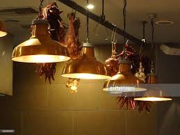 image of stylish hanging copper kitchen lamps lights in row stock