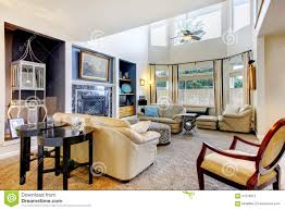large tall living room with many windows and cream furniture