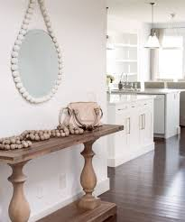 sarah and kevin swanson s seaside inspired home an oversized mirror from the cross decor design in vancouver makes a big statement in the front hallway