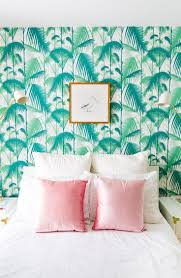 bedroom with botanical wallpaper and pink accent pillows color